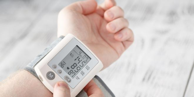 a man checking his blood pressure at home with electronics